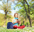Young female student with headphones and tablet sitting in park shot a tilt shift lens Royalty Free Stock Photo