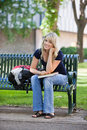 Young female student sitting on bench portrait of smiling at college campus Stock Photography