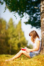 Young female student studying outdoors in the autumn. Royalty Free Stock Photo