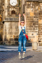 Young female traveler jumping with joy at the Old Town Square in Prague.