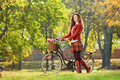 Young female walking with bicycle in park a Stock Images