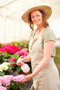 Young female wearing a hat watering the flowers Royalty Free Stock Photos