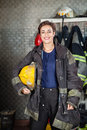 Young firewoman holding helmet at fire station portrait of happy while standing Royalty Free Stock Images
