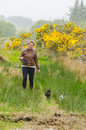 Young fisher woman with a rode walking her cats in ireland connemara Stock Photography
