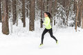 Young fit athlete woman running at forest sprinting during winter training outside in cold snow weather Royalty Free Stock Photography
