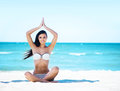 Young, fit and beautiful girl meditating on the beach Royalty Free Stock Photo