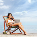 A young and fit brunette relaxing on a beautiful beach Stock Image