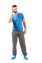 Young fit guy in sportswear talking on the mobile phone looking away full body length portrait isolated over white background Royalty Free Stock Image
