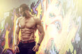 Young fit macho man posing in front of graffiti wall Royalty Free Stock Photo
