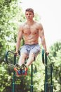 Young fit man doing push ups on bars Royalty Free Stock Photo