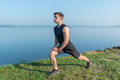 Young fit man stretching legs outdoors doing forward lunge. Royalty Free Stock Photo