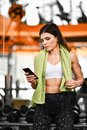 stock image of  Young fit woman using smartphone at gym
