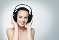 A young and fit teenage girl listening to music in headphones the image is taken on light grey background Royalty Free Stock Photos