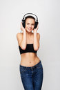 A young and fit teenage girl listening to music in headphones the image is taken on light grey background Stock Images