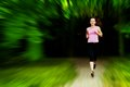 Young fit woman does running jogging training in a park motion Stock Photo