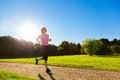 Young fit woman does running jogging training in a park at summer sunny day Royalty Free Stock Photos