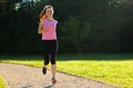 Young fit woman does running jogging training in a park at summer sunny day Stock Image