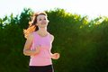 Young fit woman does running jogging training in a park at summer sunny day Stock Photos