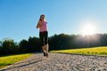 Young fit woman does running jogging training in a park at summer sunny day Stock Images