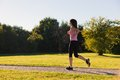 Young fit woman does running jogging training in a park during sunset Stock Image