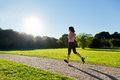 Young fit woman does running jogging training in a park during sunset Stock Photo