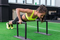 Young fit woman doing horizontal push-ups with bars in gym. Royalty Free Stock Photo
