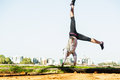 Young fit woman doing simple acrobatics exercise sporty routine in autumn park with city at background Stock Photo