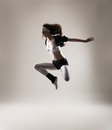 A young and fit woman jumping in sporty clothes