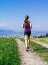 Young fit woman running down gravel road photo of a jogging and exercising on a country path lake and city in the distance slight Royalty Free Stock Photo