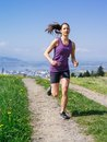 Young fit woman running in spring photo of a jogging and exercising on a country path lake and city the distance slight motion Stock Photo