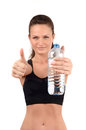 Young fit woman showing thumbs up gesture with bottle of water in the hands blur on model focus on isolated on white Royalty Free Stock Images