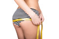 Young fit woman wearing striped panties, holding measuring tape with her hands on thigh and ass, isolated a white Royalty Free Stock Photo