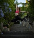 Young fitness pretty girl jumps on the stairs on the street in the summer evening