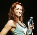 Young fitness woman beautiful with mineral water over black background Stock Images