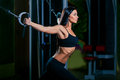 Young fitness woman execute exercise with exercise machine cable crossover in gym horizontal photo Royalty Free Stock Images