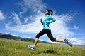 Young fitness woman runner running on beautiful trail in grassland Royalty Free Stock Photo