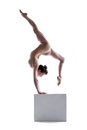 Young flexible woman posing on cube in studio Royalty Free Stock Image