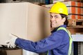Young foreman lifting cardboard box portrait of a warehouse worker Stock Photo