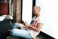 Young freelancer man connecting to wireless via notebook and mobile phone attractive hipster student typing text message on his Royalty Free Stock Photo