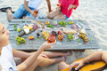 Young friends drinking rose wine on summer beach picnic Royalty Free Stock Photo
