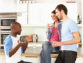 Young Friends Enjoying Glass Of Wine In Kitchen Royalty Free Stock Image