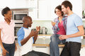 Young Friends Enjoying Glass Of Wine In Kitchen Stock Photos