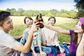 Young friends enjoying picnic and drinking beer happy Stock Photo
