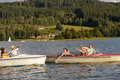 Young friends having fun in motorboats waving and splashing water Royalty Free Stock Images