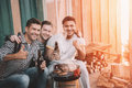 Young friends making barbecue and drinking beer on porch with back light Royalty Free Stock Photo