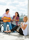 Young friends play the guitar and trumpet Royalty Free Stock Photos