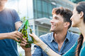 Young friends toasting with beer closeup shot of bottles of happy smiling guys and women drinking outdoor carefree group of Stock Photos