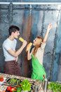 Young funny couple playing corn cobs kitchen like microphones Stock Photos