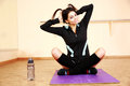 Young funny fit woman sitting on the yoga mat at gym Stock Photos