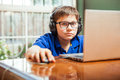 Young gamer using a laptop little with headphones playing video games on computer Stock Photography